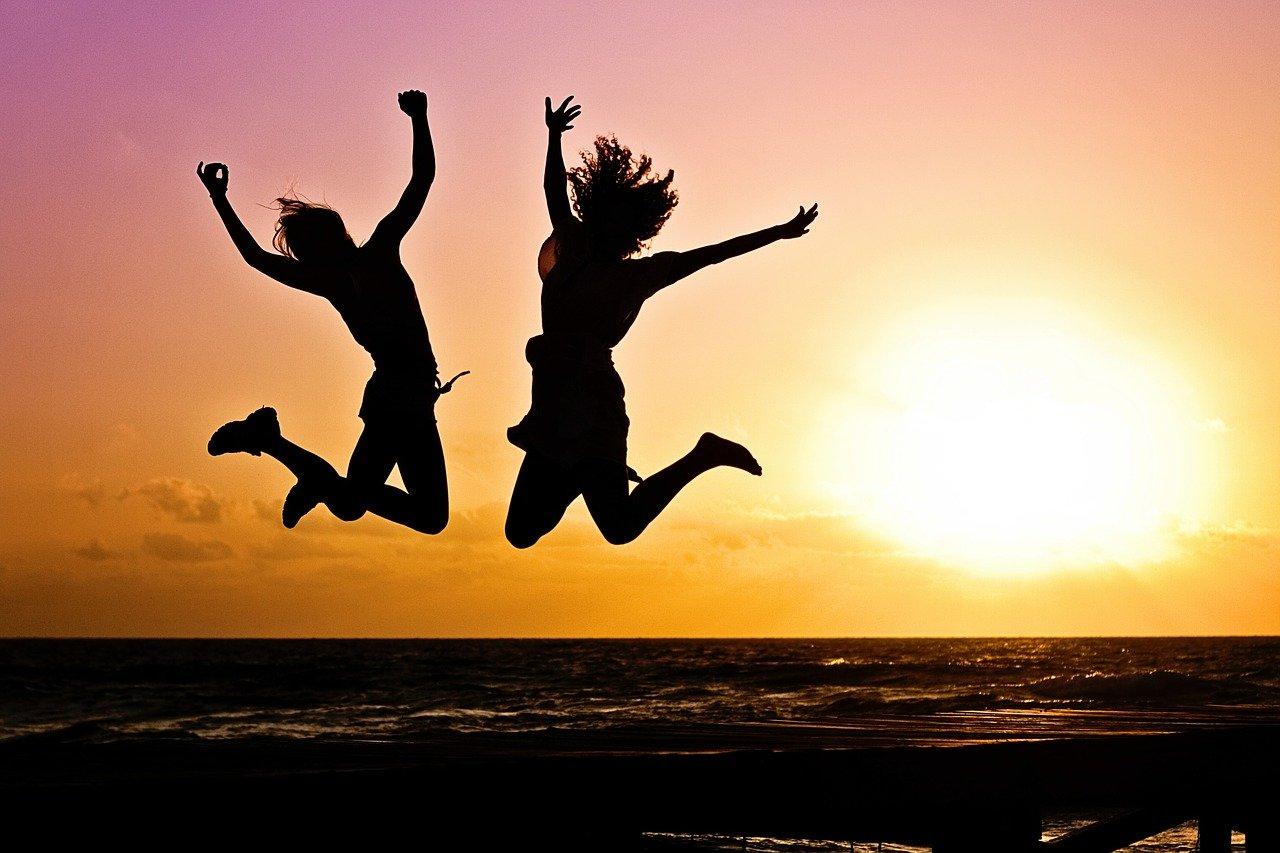 Zwei Personen springen hoch glücklich Sonnenuntergang